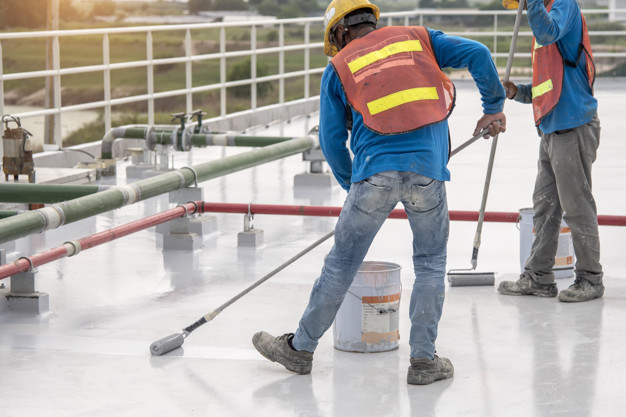 Construction worker coating epoxy paint at roof slab for water proof protection